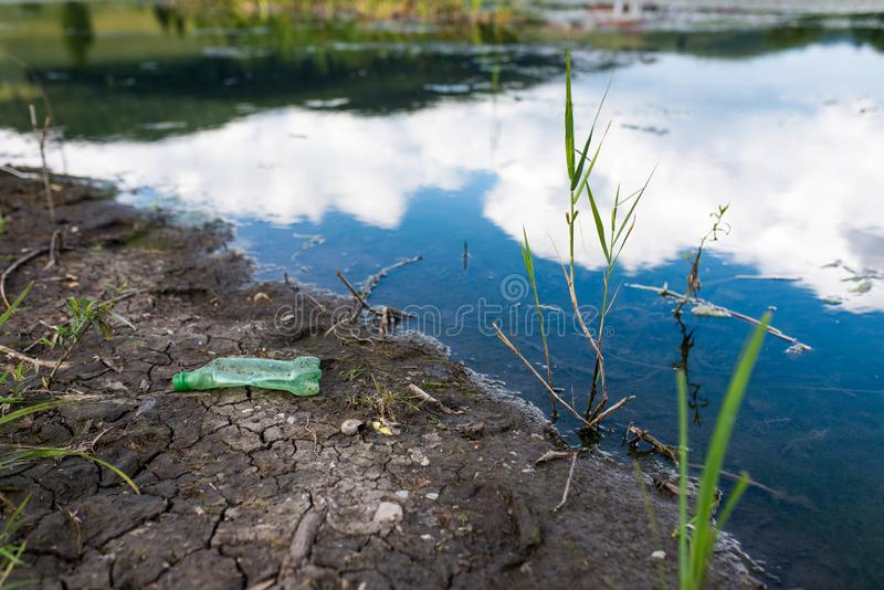 Garrafa plástica verde perto do lago limpo fotografia de stock