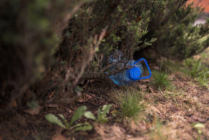 Garrafa pl?stica grande azul que encontra-se na terra na ?rvore em uma floresta do parque - jogada para fora n?o reciclou - lixo  foto de stock