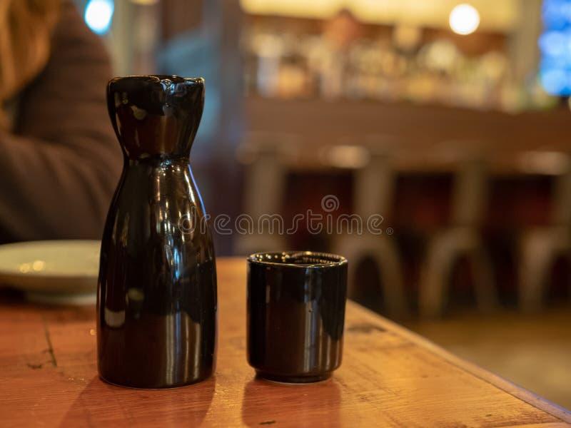 Garrafa preta e vidro da causa que sentam-se na tabela no espaço para refeições imagens de stock royalty free