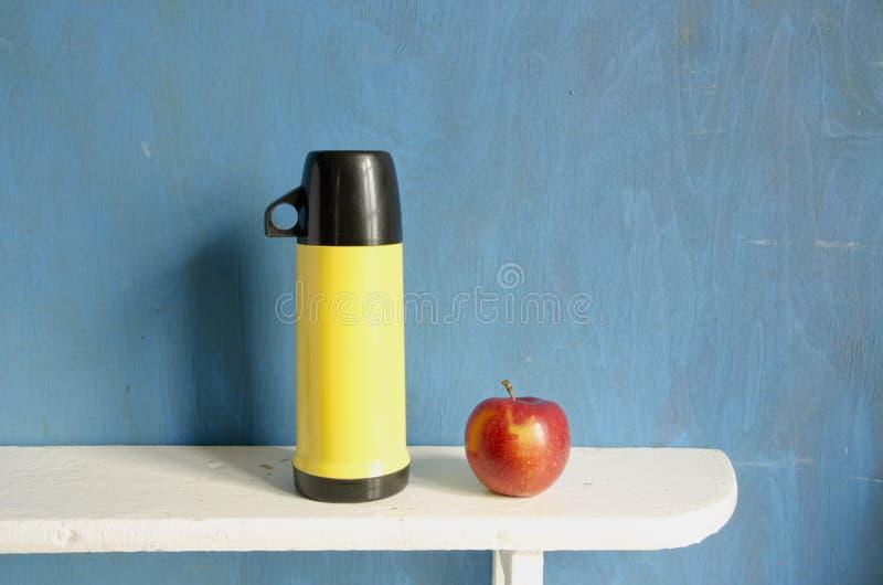 Garrafa térmica do chá e maçã vermelha na prateleira de madeira imagem de stock royalty free