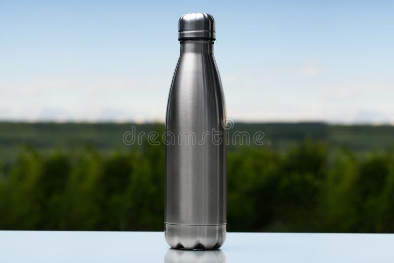 Garrafa térmica inoxidável, garrafa de água no céu e fundo da floresta fotos de stock