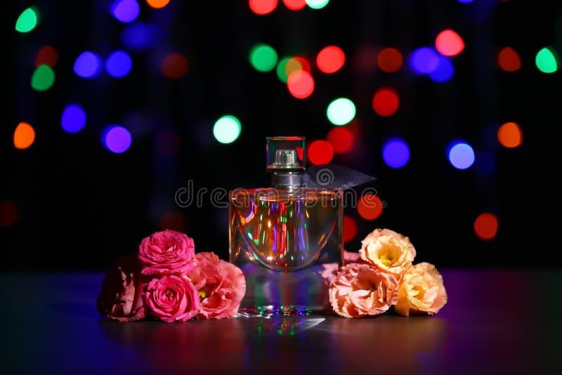 Garrafa transparente do perfume com as flores bonitas na tabela escura contra luzes borradas fotografia de stock