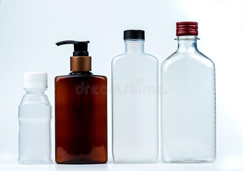 Garrafa vazia do plástico e a de vidro com tampão e bomba com a etiqueta preta isolada no fundo branco Garrafa dos produtos farma fotos de stock