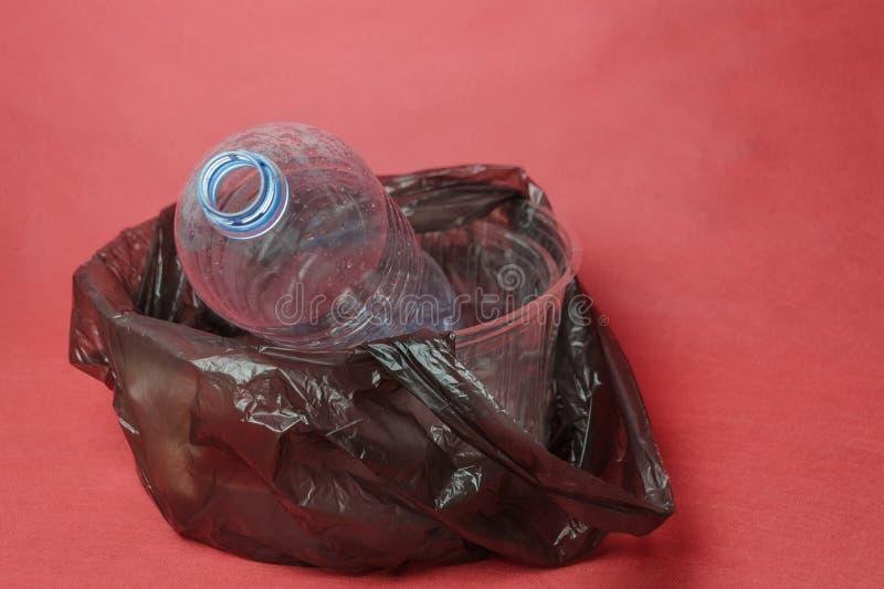Garrafa vazia pl?stica em um saco preto no recipiente no fundo vermelho Conceito da polui??o ambiental pelo lixo pl?stico fotografia de stock