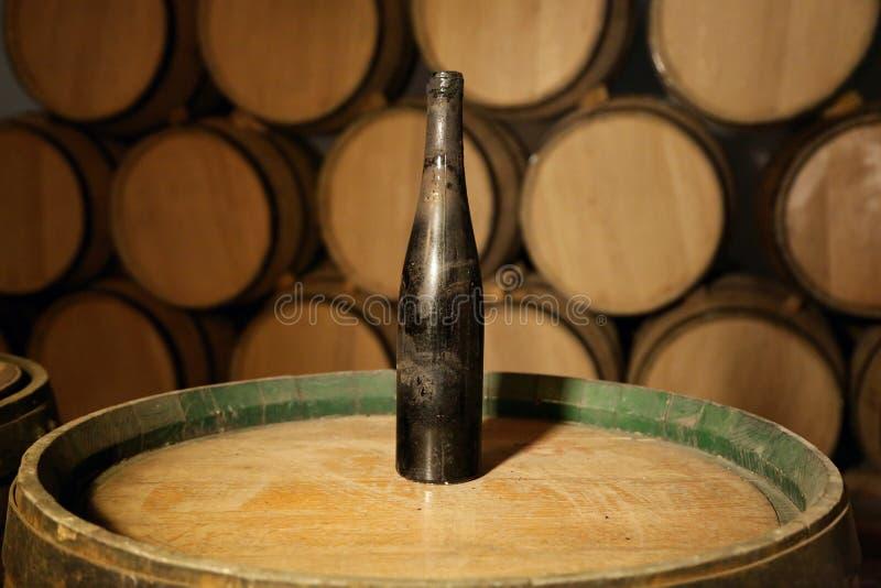 Garrafa velha do vinho em um tambor na adega da adega fotos de stock