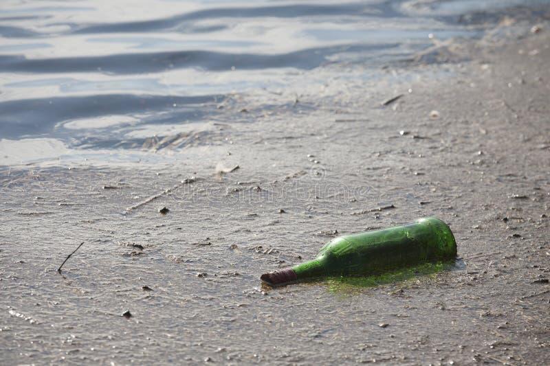 Garrafa verde em uma lagoa, em uma poluição e em uma desordem imagem de stock