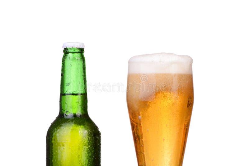 Garrafa verde refrigerada com condensado e um vidro da cerveja pilsen da cerveja fotografia de stock