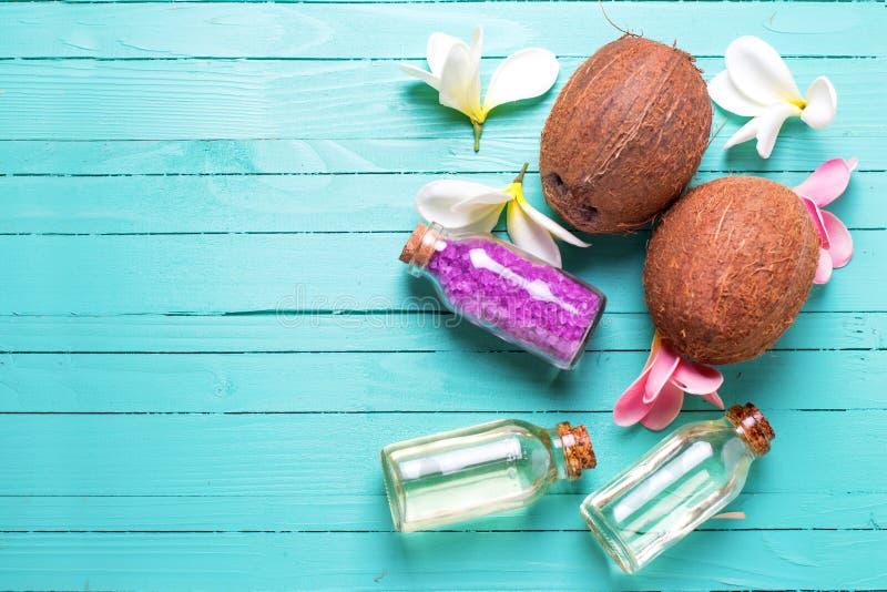 Garrafas com óleo de coco, cocos e sal do mar em w brilhante fotografia de stock