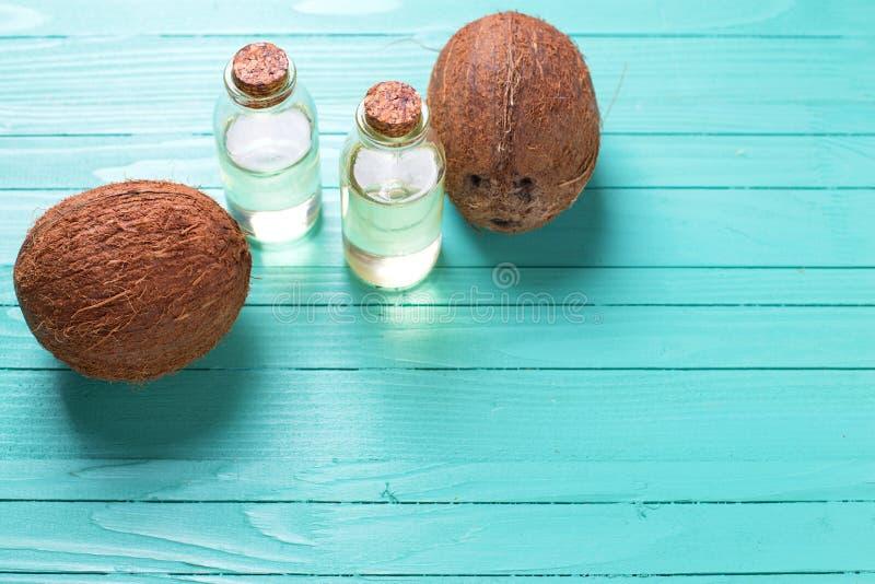 Garrafas com óleo de coco no backgroun de madeira de turquesa brilhante imagens de stock royalty free