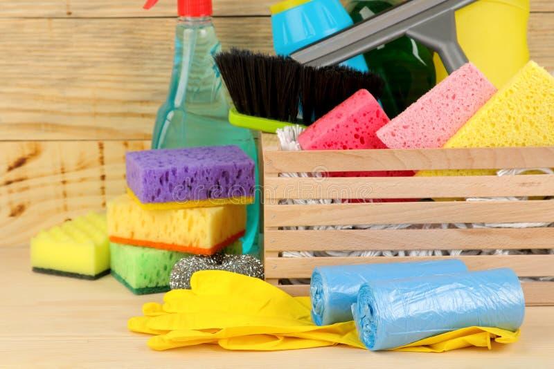Garrafas com as ferramentas detergentes e limpando em uma gaveta em um fundo de madeira natural Limpeza Produtos de limpeza imagem de stock
