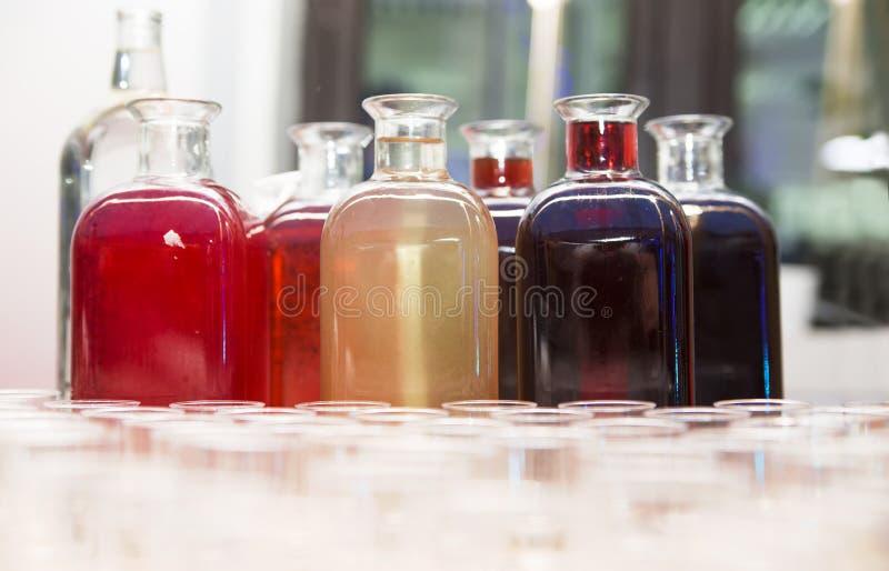 Garrafas com tinturas caseiros e vidros na tabela foto de stock