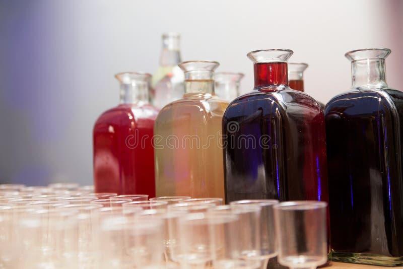 Garrafas com tinturas caseiros e vidros na tabela fotografia de stock royalty free