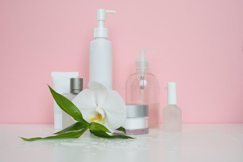 Garrafas cosméticas brancas em um fundo da rosa foto de stock