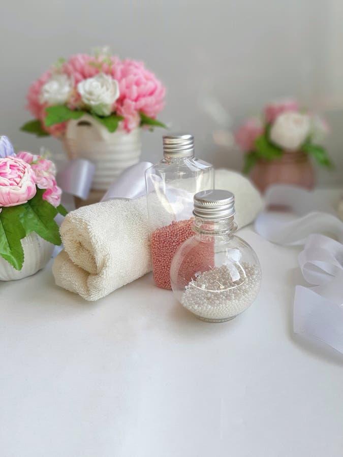 Garrafas cosméticas da pérola, toalha, ramalhete de flores do sabão no fundo branco foto de stock