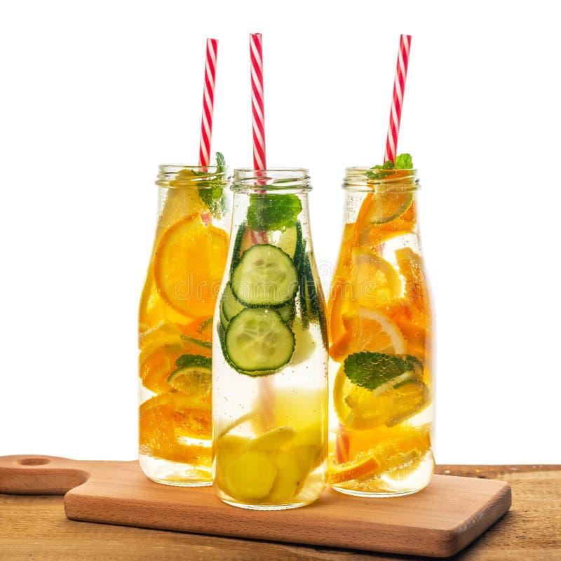 Garrafas da água infundida da desintoxicação com limão, laranja, cal, hortelã do galho, pepino, gengibre e palhas no fundo de mad fotografia de stock royalty free