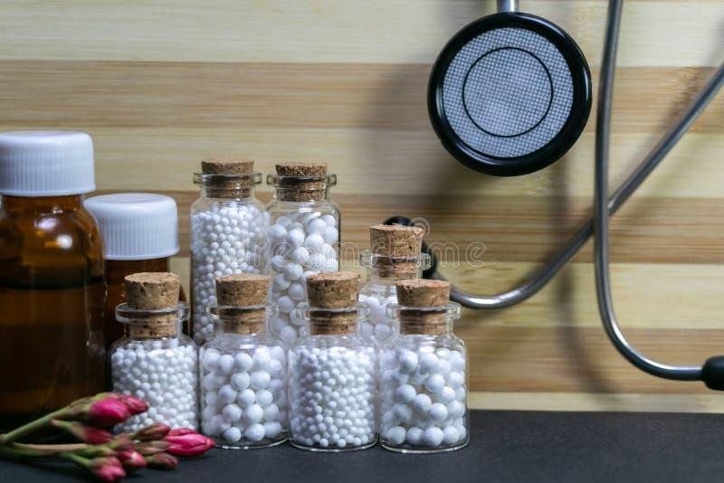 Garrafas da medicina homeopaticamente em seguido que consistem em comprimidos, em estetoscópio e na flor em botão cor-de-rosa na  imagens de stock