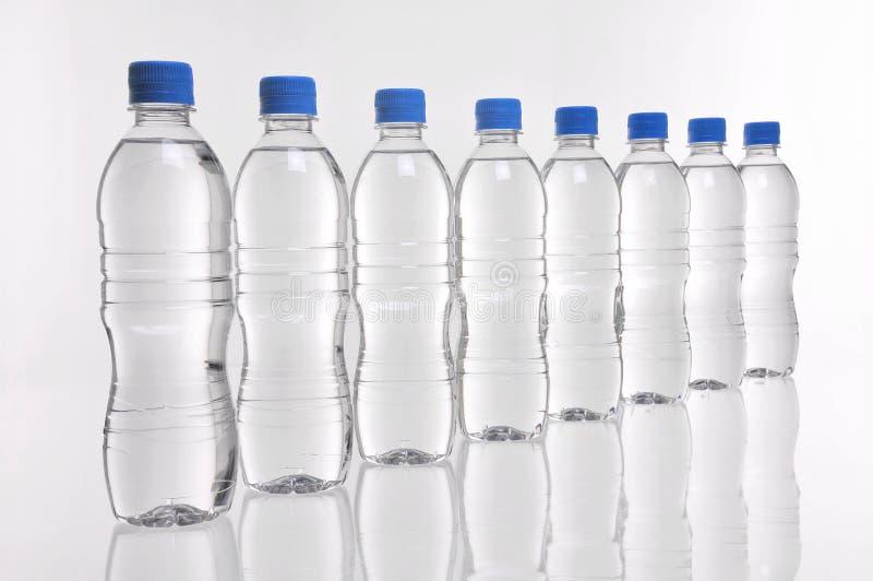 Garrafas de água em uma linha fotos de stock