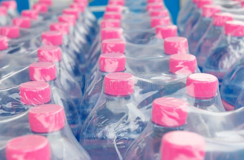 Garrafas de água na película de plástico fotos de stock