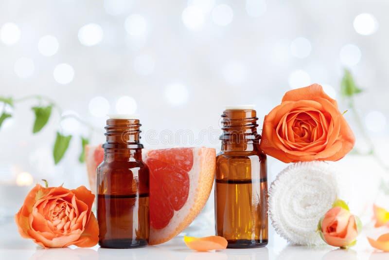 Garrafas de óleo essencial com toalha, toranja e as flores cor-de-rosa na tabela branca Termas, aromaterapia, bem-estar, fundo da imagem de stock