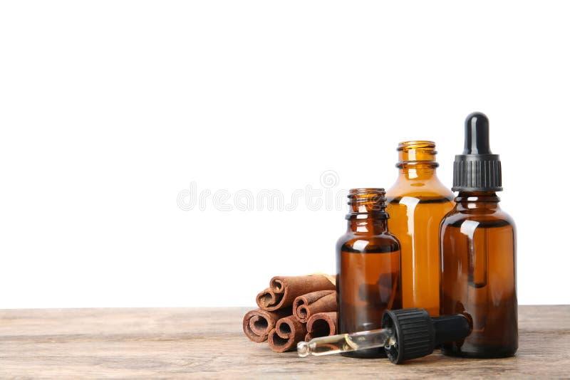 Garrafas de óleos essenciais e de varas de canela na tabela de madeira contra o fundo branco fotografia de stock royalty free