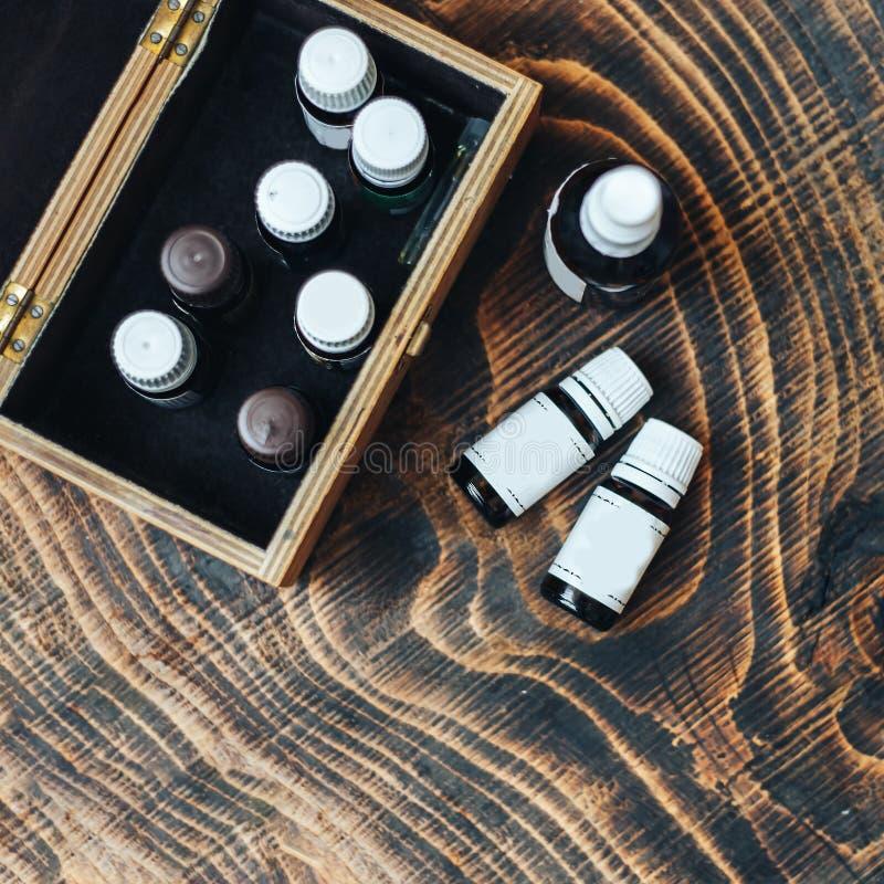 garrafas de óleos essenciais no fundo de madeira imagens de stock