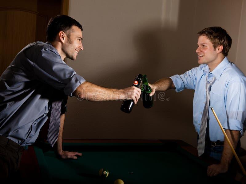 Garrafas de cerveja do tinido dos homens novos na sinuca imagens de stock