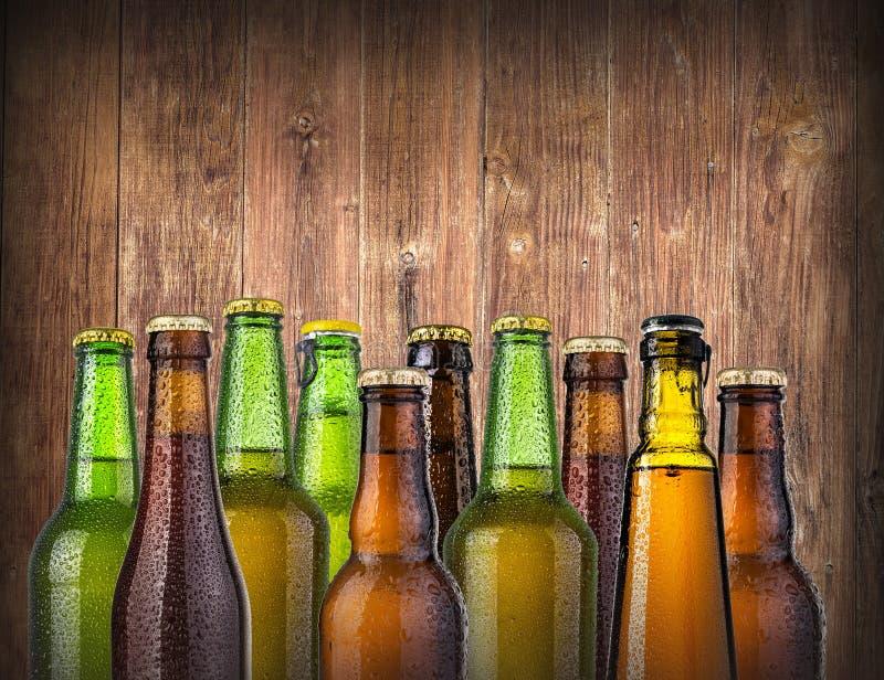 Garrafas de cerveja em de madeira imagens de stock royalty free