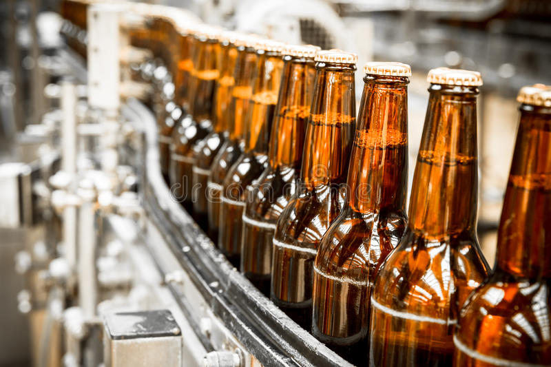 Garrafas de cerveja na correia transportadora imagens de stock