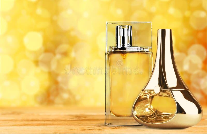 Garrafas de perfume aromáticas no fundo dourado imagens de stock