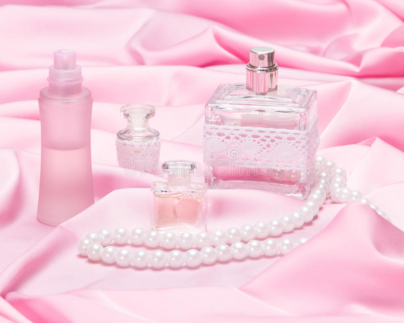 Garrafas de perfume cercadas pela tela de seda fotos de stock