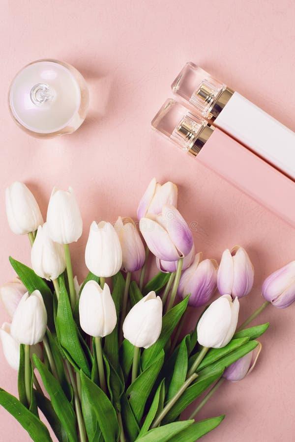 Garrafas de perfume cercadas por flores fotos de stock