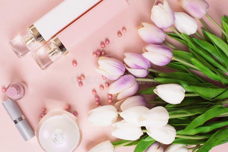 Garrafas de perfume cercadas por flores e por pérolas no backgro cor-de-rosa foto de stock royalty free