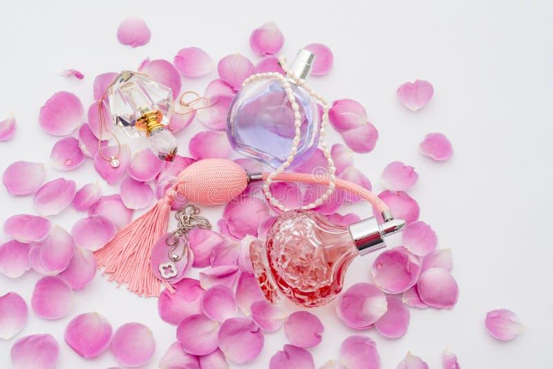 Garrafas de perfume com as colares entre as pétalas da flor no fundo branco Perfumaria, cosméticos, coleção da fragrância fotos de stock royalty free