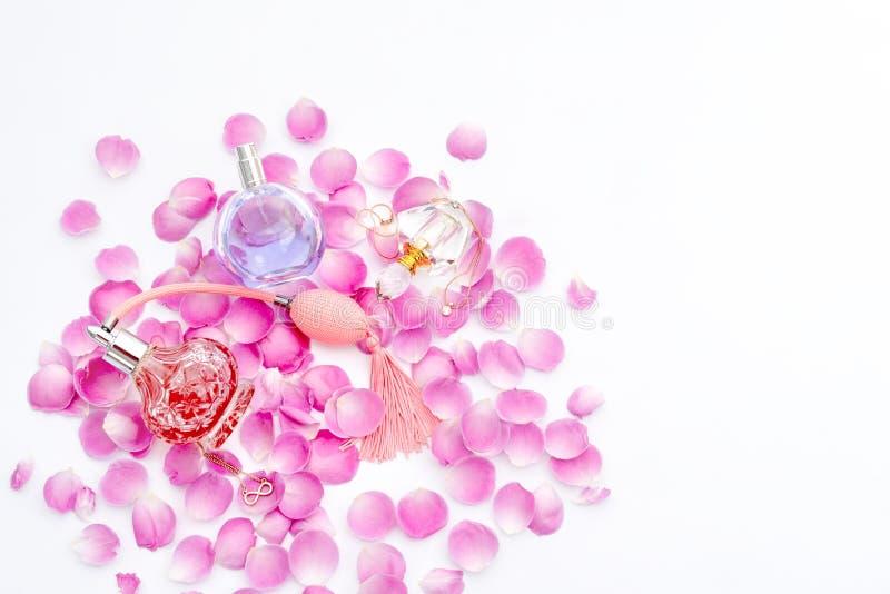 Garrafas de perfume com as pétalas da flor no fundo branco Perfumaria, cosméticos, coleção da fragrância fotos de stock royalty free
