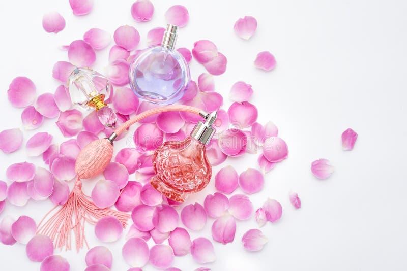 Garrafas de perfume com as pétalas da flor no fundo branco Perfumaria, cosméticos, coleção da fragrância fotografia de stock royalty free
