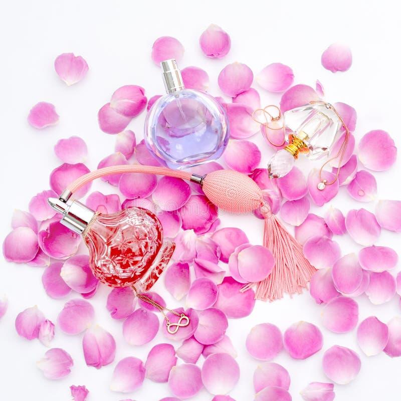Garrafas de perfume com as pétalas da flor no fundo branco Perfumaria, cosméticos, coleção da fragrância imagens de stock