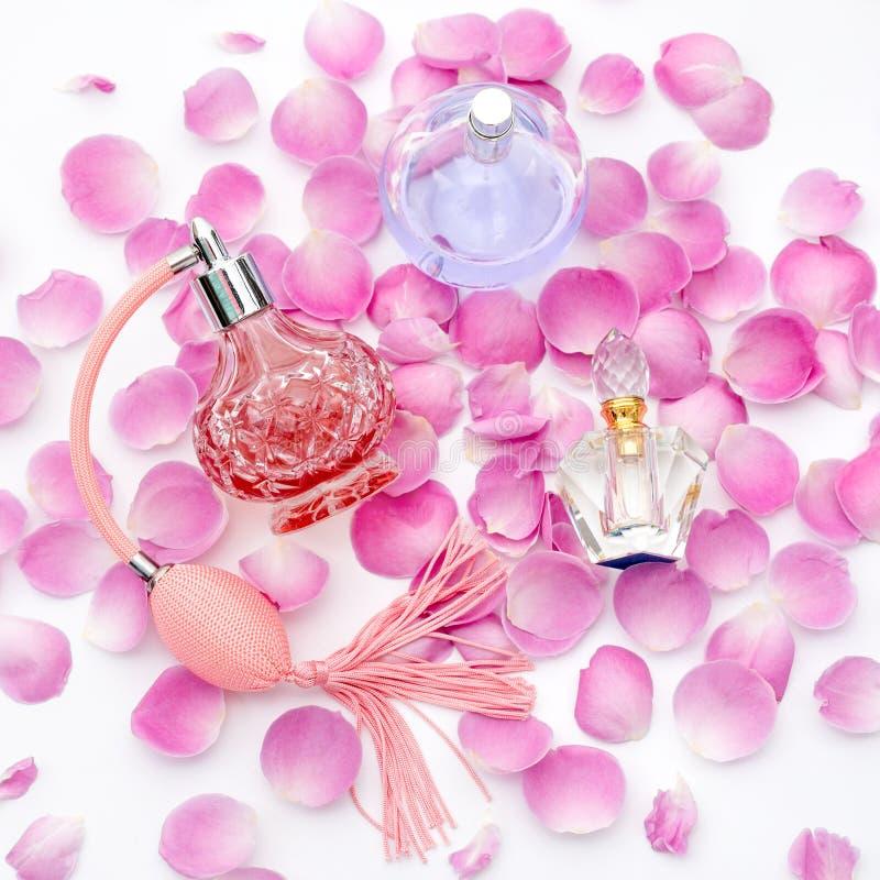 Garrafas de perfume com as pétalas da flor no fundo branco Perfumaria, cosméticos, coleção da fragrância imagem de stock royalty free
