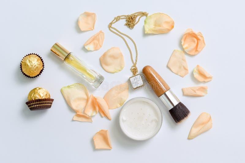Garrafas de perfume com as pétalas das flores no fundo branco Coleção da perfumaria, dos cosméticos, da joia e da fragrância fotos de stock royalty free