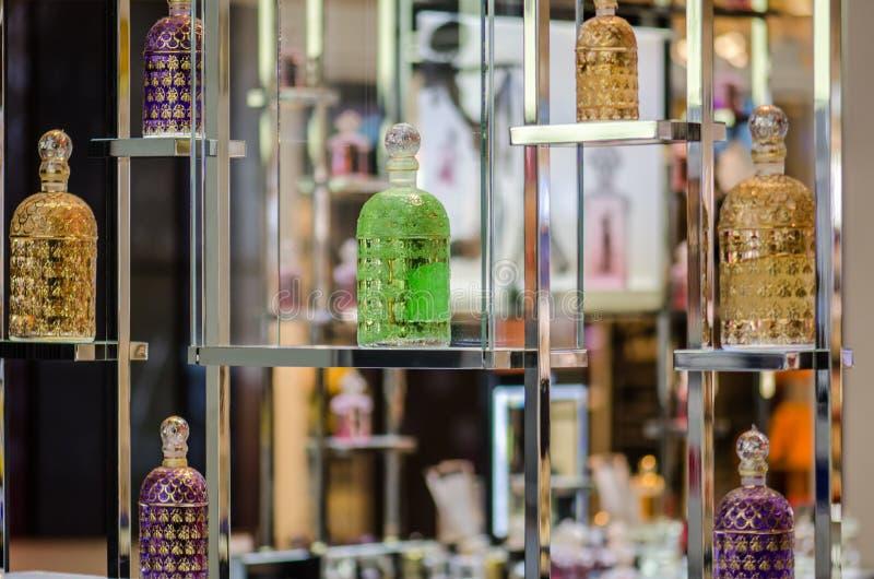 Garrafas de perfume diferentes coloridas indicadas na loja da fragrância imagens de stock
