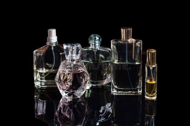 Garrafas de perfume diferentes com reflexões no fundo preto com espaço para o texto Perfumaria, cosméticos, fragrância imagem de stock
