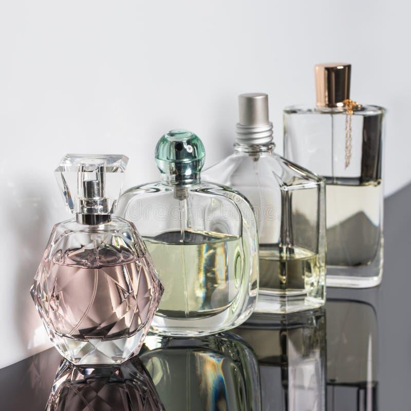 Garrafas de perfume diferentes com reflexões Perfumaria, cosméticos fotos de stock
