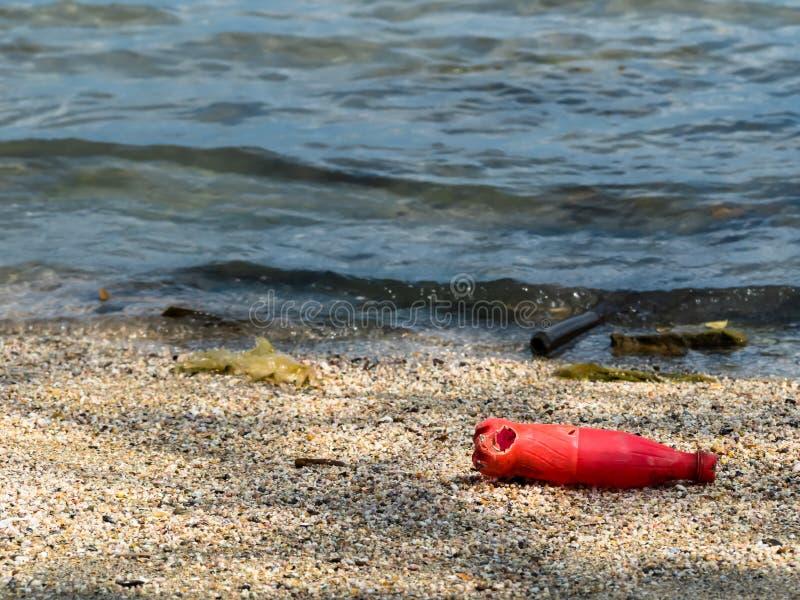 Garrafas de soda vermelhas que foram deixadas por turistas na praia fotos de stock royalty free