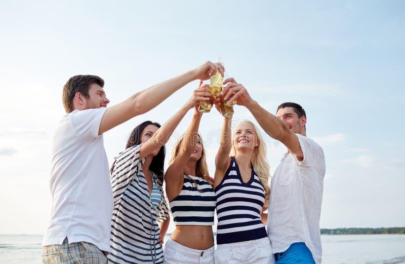 Garrafas de sorriso do tinido dos amigos na praia imagens de stock