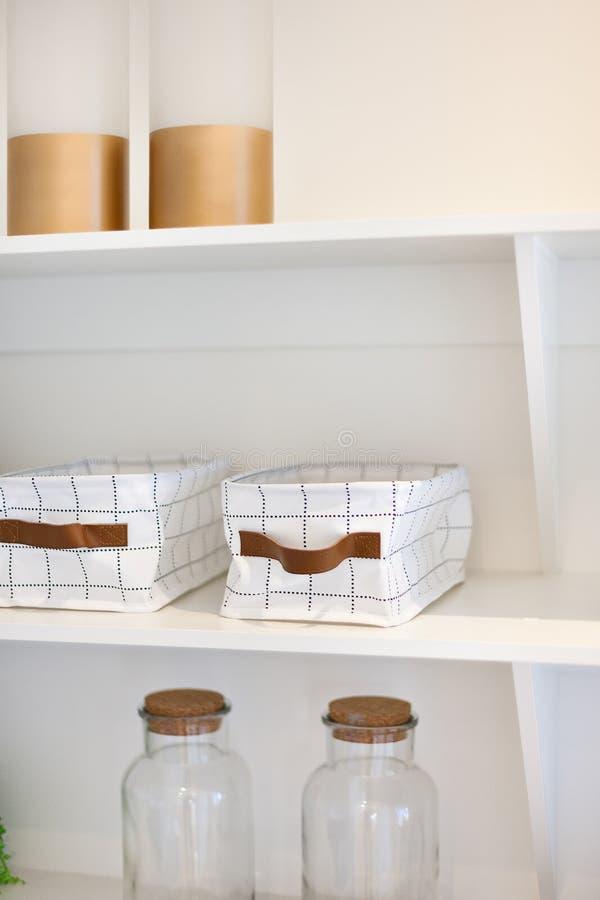 Garrafas de vidro e cestas do vestuário na prateleira de madeira fotografia de stock