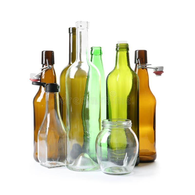 Garrafas de vidro e frasco vazios no branco Reciclando o problema fotografia de stock