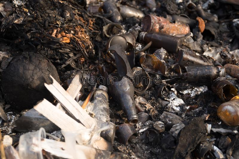 Garrafas de vidro e lixo quebrados no lixo queimado fotografia de stock royalty free