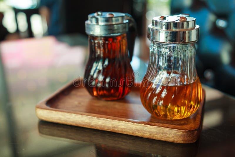 Garrafas de vidro na bandeja de madeira na tabela, contendo xaropes líquidos da avelã e do caramelo para o café do tempero, a beb fotografia de stock royalty free