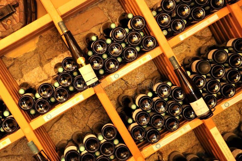 Garrafas de vinho em prateleiras de madeira fotografia de stock royalty free
