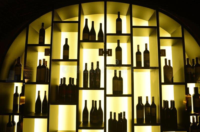 Garrafas de vinho tinto, prateleiras iluminadas, negócio imagens de stock royalty free