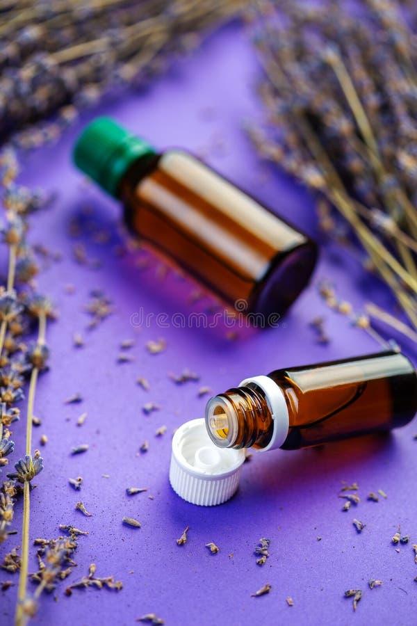 Garrafas do óleo essencial do lavandula, grupo da flor roxa secada da alfazema fotografia de stock